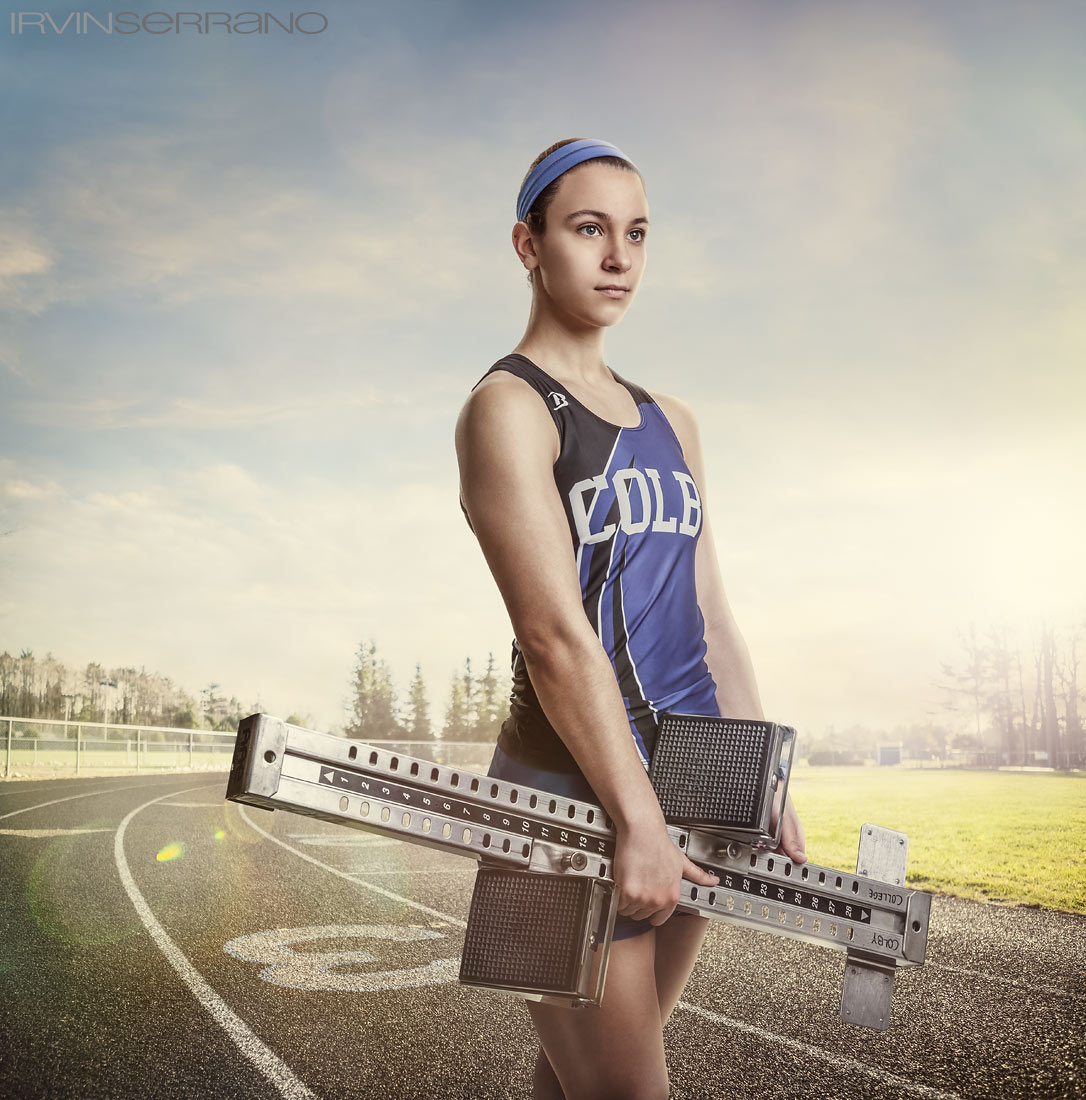 A female collegiate athlete holds her starting blocks on the track at Colby College.