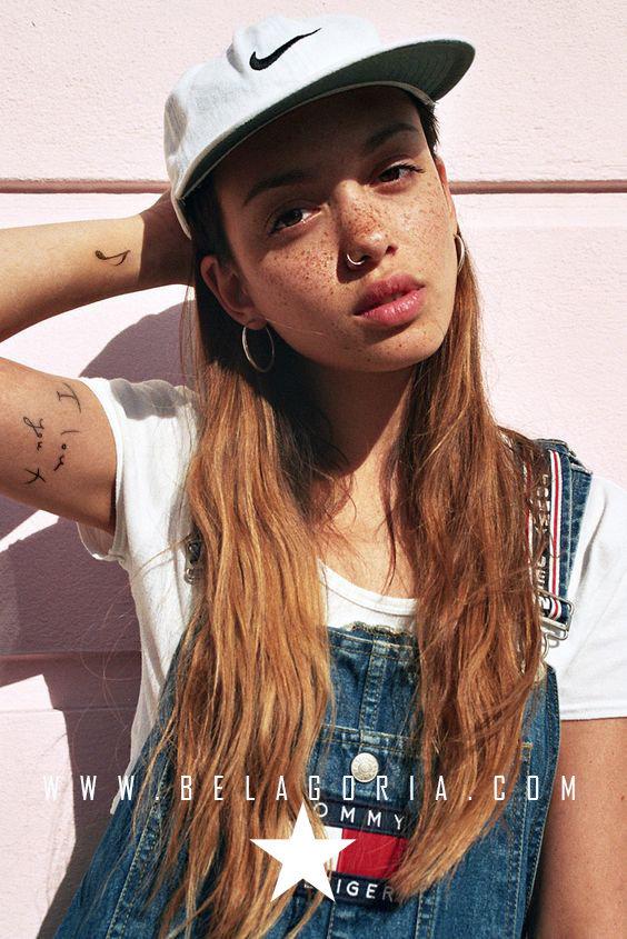 Chica apoyada en pared lleva tatuaje de nota musical en la muñeca