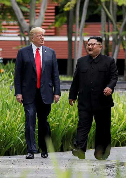 US President Donald Trump and North Korea's leader Kim Jong-un walk together before their working lunch during their summit at the Capella Hotel on the resort island of Sentosa, Singapore, Tuesday (12/06).