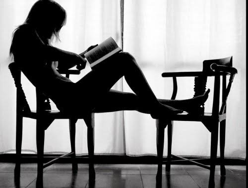 Mujer sexy desnuda leyendo un libro semi tumbada en dos sillas.
