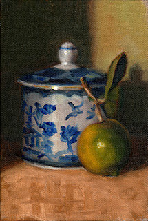 Oil painting of a blue and white porcelain sugar bowl beside a lime with leaf and stem attached.