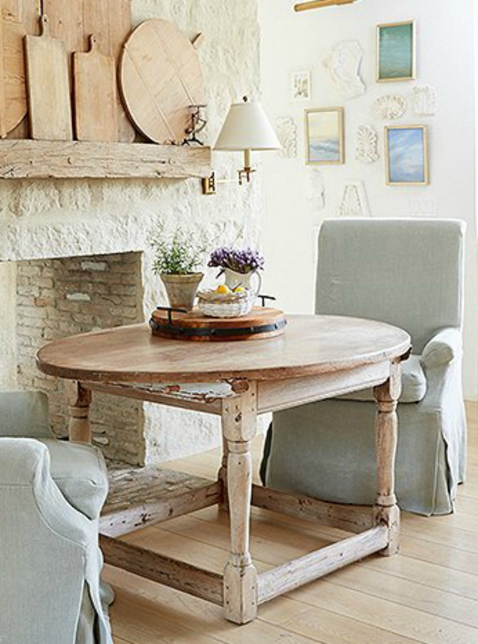 Rustic bread boards massed on a wood beam mantel of limestone fireplace in a romantic #farmhousekitchen