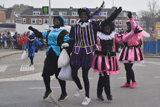 Costumed Piets skipping with their sacks of goodies, Zaandam, The Netherlands