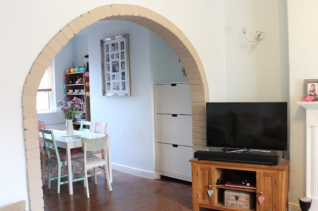 living room and dining room separated by cream brick arch