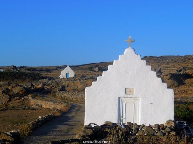 białe greckie kaplice na tle jałowych skał i błękitnego nieba Mykonos Grecja