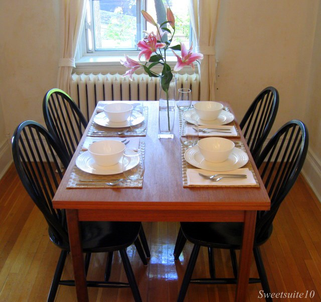 Black Windsor chairs around a Teak Dining Table