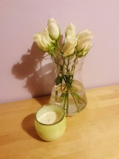Jar of white roses with green candle
