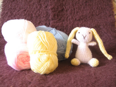 Three skeins of baby yarn next to which sits a white lop-eared amigurumi bunny, no bigger than a skein of yarn.  The bunny has a white body, head, arms and legs with yellow feet and very long yellow ears which almost touch the ground when the rabbit is seated.The face is embroidered with black thread.