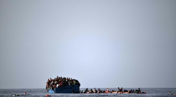 """Migrants wait to be rescued by members of Proactiva Open Arms NGO in the Mediterranean Sea, some 12 nautical miles north of Libya, on October 4, 2016. By Aris Messinis (AFP) Aboard the Astral (Italy) (AFP) - At least 22 Europe-bound migrants were confirmed dead on Tuesday in an overloaded wooden boat off Libya, an AFP photographer witnessed, on a day of frantic rescues in the Mediterranean.  Photographer Aris Messinis, who was able to go on board the vessel, said many of the dead had suffocated.  """"It was a wooden vessel and there were about 1,000 people on three levels. I counted 22 bodies and there are still others in the hold,"""" he said by telephone.  Messinis was travelling on the Astral, a ship chartered by Spanish NGO ProActiva Open Arms, which rescues migrants at sea.  Towards 2000 GMT the Astral rescuers moved back to allow the Italian navy to take care of the survivors and retrieve the bodies, the photographer said."""