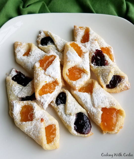 powdered sugar dusted apricot and mixed berry kolacky on plate