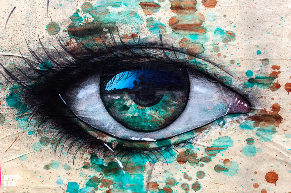 Street Artist My Dog SIghs pasteups of a large eye jn London, UK