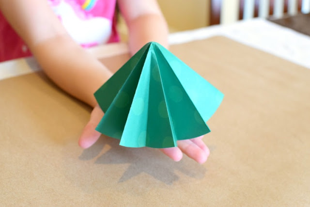 Folded paper Christmas tree ornament craft for kids. Origami is a great fine motor work activity for kindergarten or elementary children!