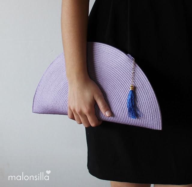 Chica sosteniendo bolso de mano color lila con borla azul klein