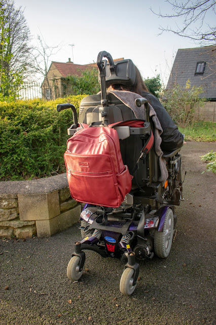 Close up of back of powerchair with red backpack on