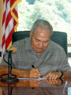 A man signs a paper at a table