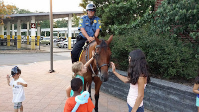 Mounted police officer, children petting the horse