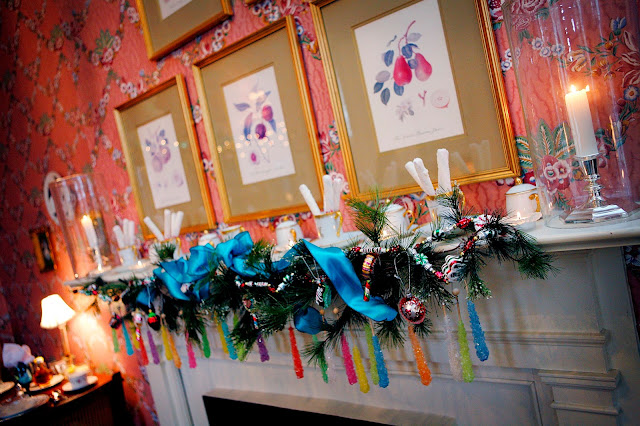 the fireplace mantel decorated with candy sugar sticks of different colors and a garland with blue bows and burning candles on the mantel with glass scones around them