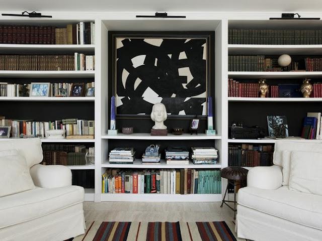 Classic home library light wood floor slip covered arm chairs built in bookshelves art