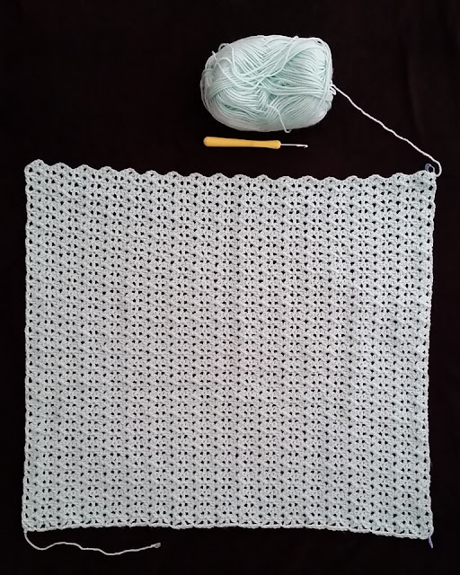 "A lacy stitch pattern of shells and trebles arranged in columns using mint-coloured 8 ply yarn. The blanket is laid out onto a black background to show the holes in the lacy pattern. Above the blanket is a bullet skein with a yellow-handled 4.25 mm aluminium crochet hook  (US size G). The handle is of the ""soft touch"" style."