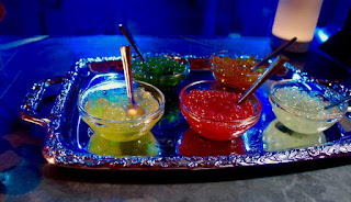 Semicircular glass clear bowls containing red, yellow and white small spherical balls of boba on a silver rectangular table with a blue cloth on a dark background