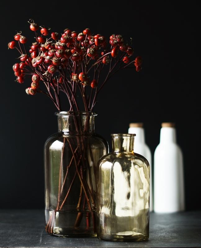Blog + Fotografie by it's me! - Hagebutten, eine braune Glasflasche und weiße Flaschen