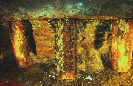 Deteriorated timber pile below concrete pile cap