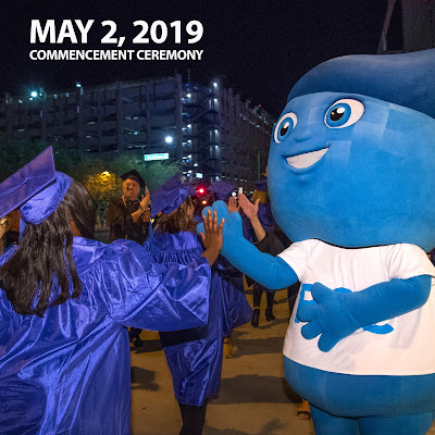 Image of 2018 commencement post ceremony celebration.  Rio mascot Splash gives a grad a high-five.