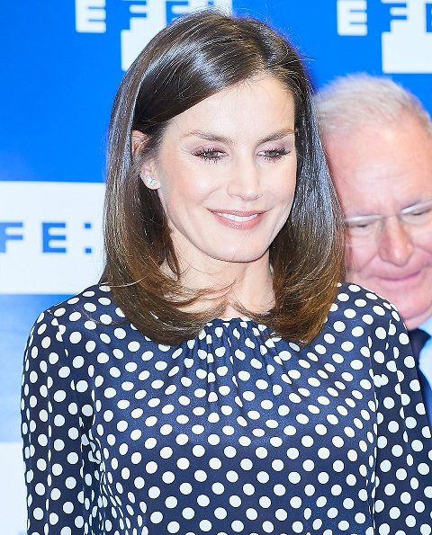 Queen Letizia wore a ecru polka dot silk top by Carolina Herrera, and a navy blue high waist wide leg  trousers by Hugo Boss