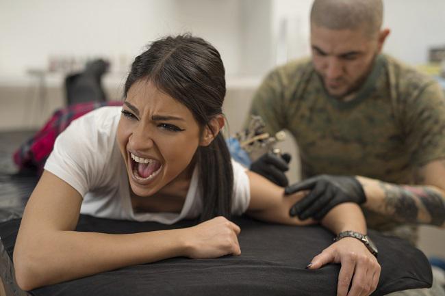 Una chica gritando de dolor mientras se tatua