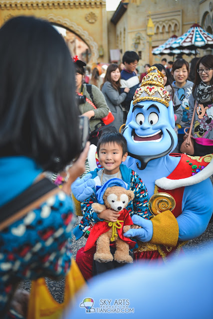 Happy kid with Aladdin's Genie and in Tokyo Disneyland