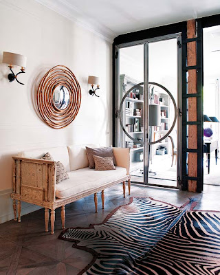 modern entryway in black and white with zebra rug and round mirror via belle vivir blog