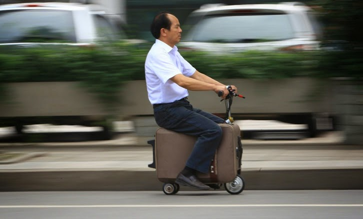 guy riding on a suitcase