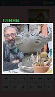 мужчина сделал скульптуру птицы из глины на столе