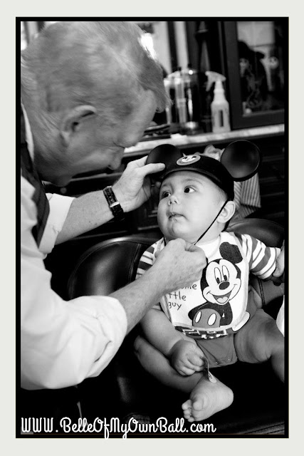 A photo of a baby receiving his first set of Mickey ears after receiving his first haircut at Harmony Barber Shop in the Magic Kingdom.