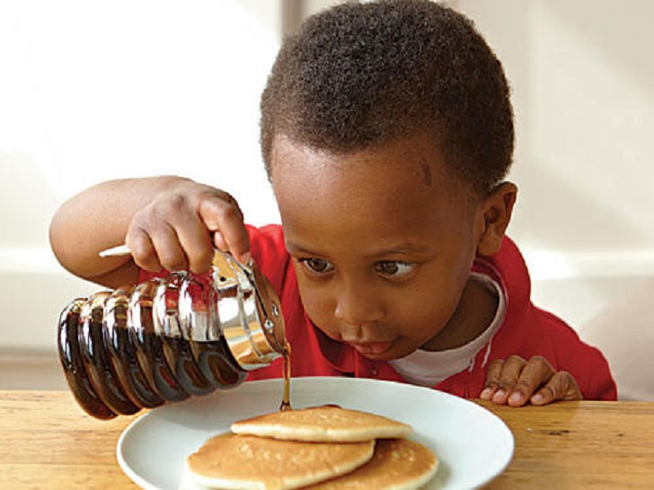 Child having pancakes syrup for breakfast