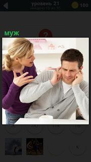 Муж за столом заткнул уши, а жена пытается ему что то сказать