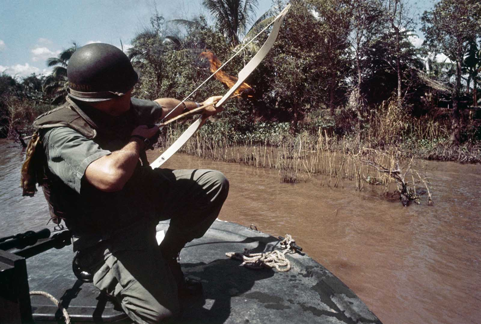 Lieutenant Commander Donald D. Sheppard, of Coronado, California, aims a flaming arrow at a bamboo hut concealing a fortified Viet Cong bunker on the banks of the Bassac River, Vietnam, on December 8, 1967.