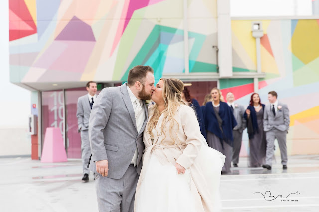 bride and groom on z belt lot rooftop in detroit kissing by graffiti