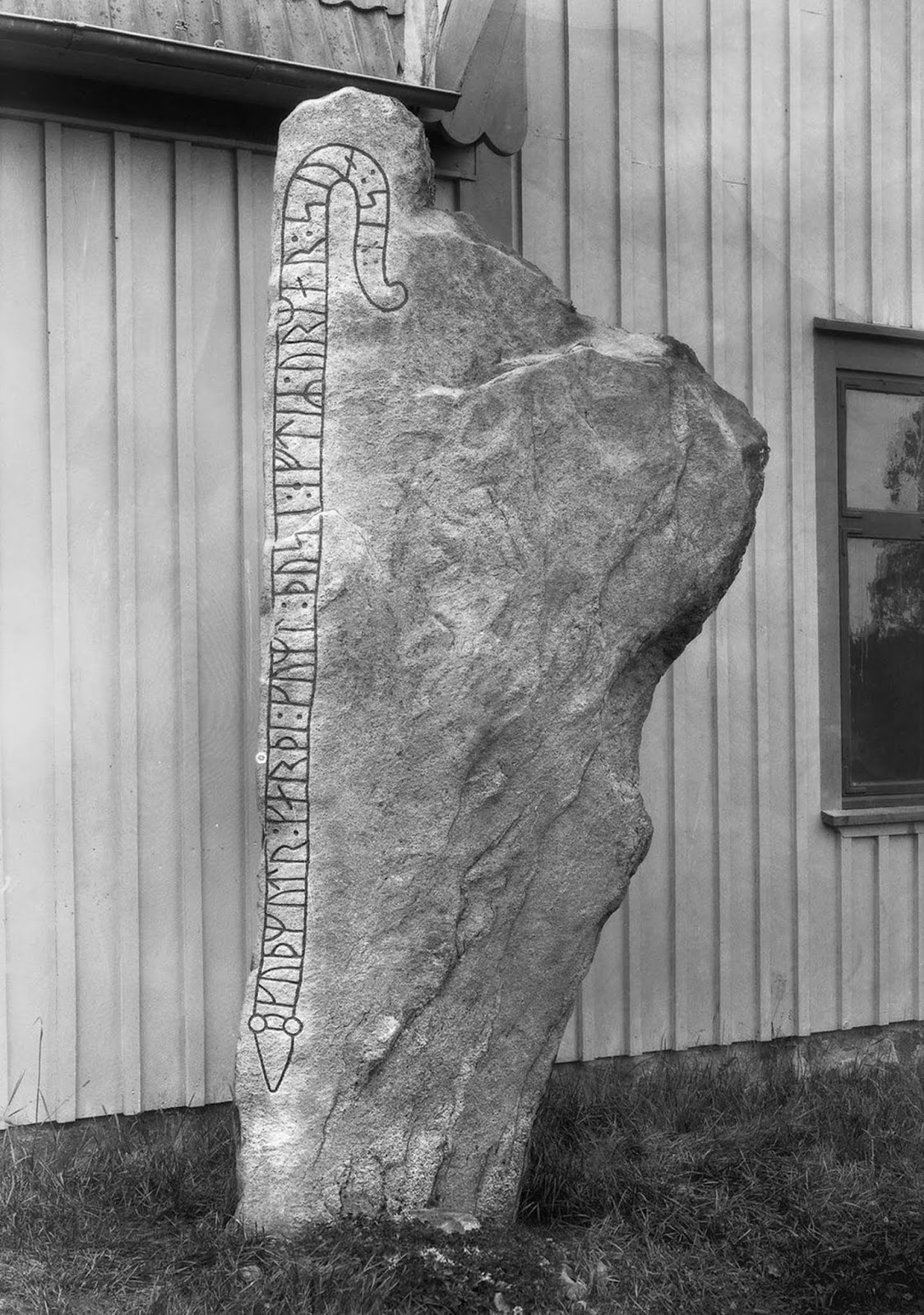 A runestone next to a house in Herrestad. The inscription reads,