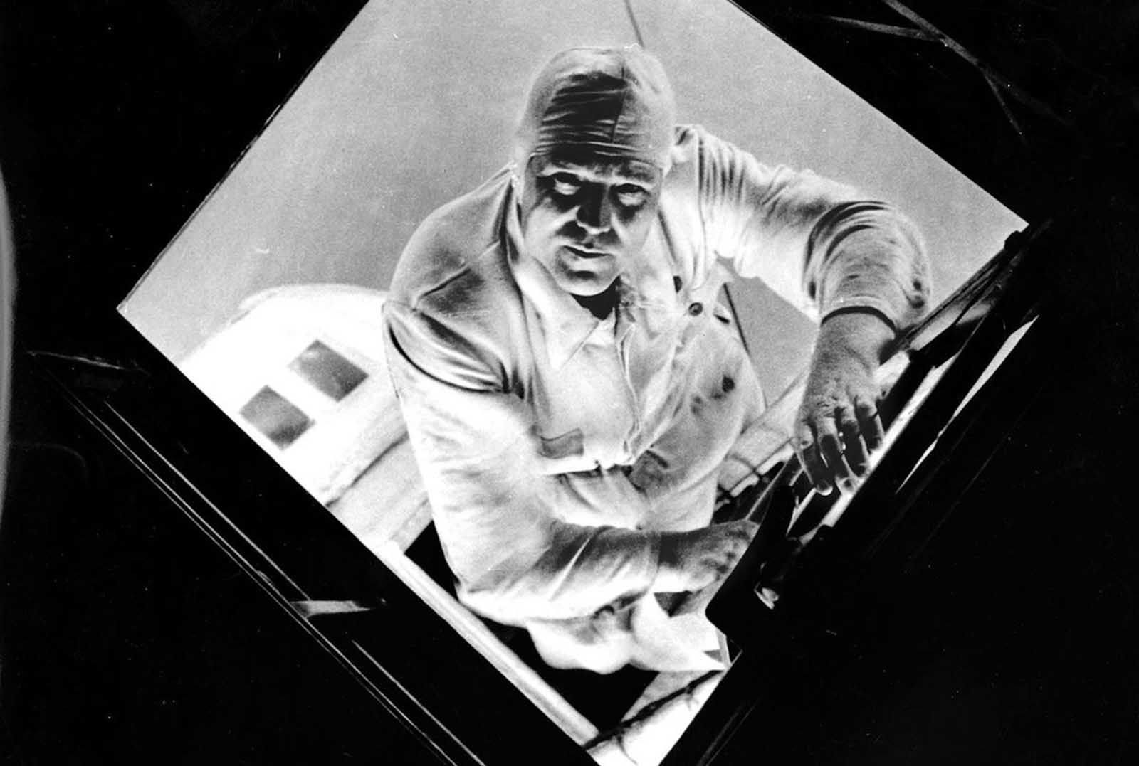 The mechanic of the rear engine gondola changes shift climbing inside the mantle of the airship, as the Graf Zeppelin sails over the Atlantic Ocean in a seven-day journey from Europe to South America, in August of 1933.
