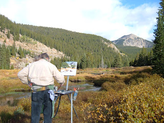 Artist painting along a small pond with beautiful mountains all around.