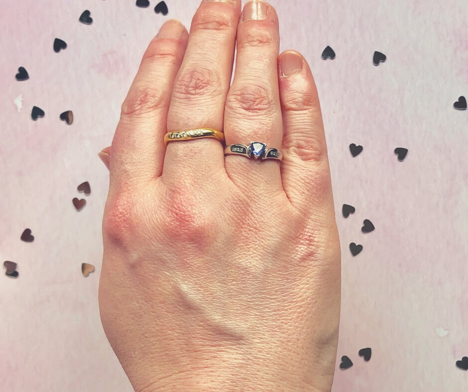 "A female hand hovers above a pink background with small silver hearts on it. The female hand has two rings on it, one is gold with 5 diamonds across the middle of it, the other is a platinum ring with a triangle shaped tanzanite stone in the centre. To each side of the tanzanite stone are 3 diamonds set into the band. Image for ""Beautiful jewellery from Kaya jewellery & WIN £40 voucher!"""