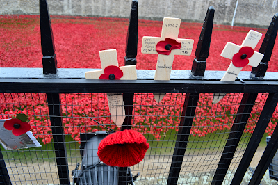 Memorial crosses and poppies stuck in a gate outside the Tower's moat.