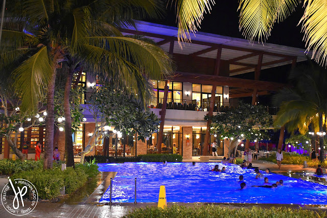 restaurant, coconut trees, people swimming at the infinity pool at night
