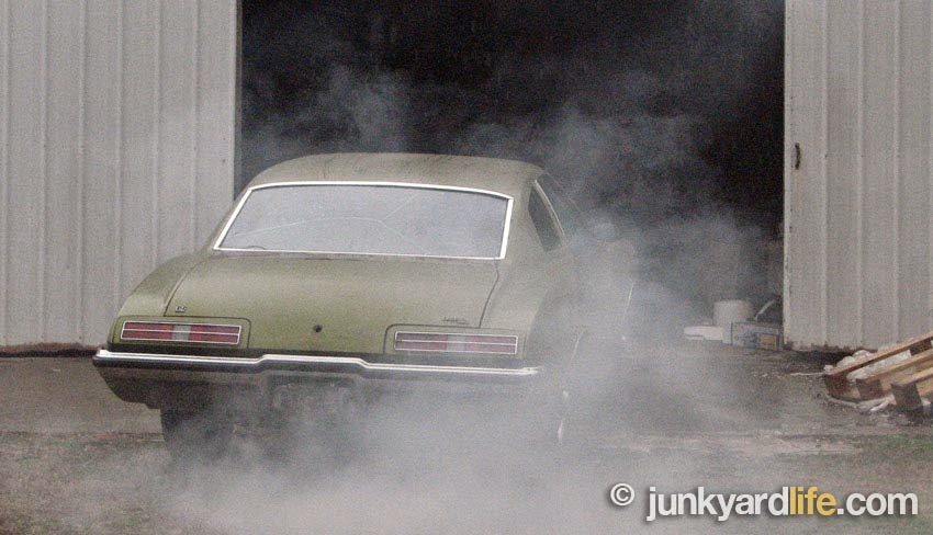 1973 Pontiac Grand Am is smoking heavily and idling outside undisclosed storage facility.