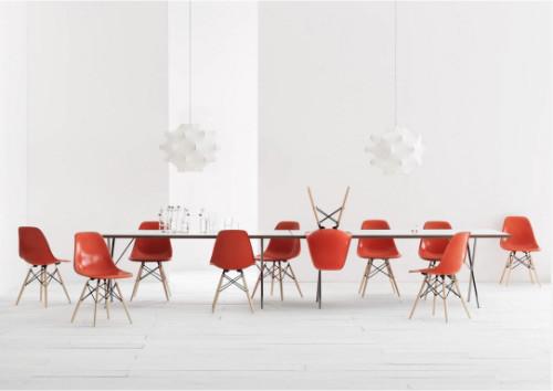 In diesem Esszimmer mit weißen Wänden und weißen Holzdielen bringen orangefarbene Eames-Stühle Farbe ins Spiel