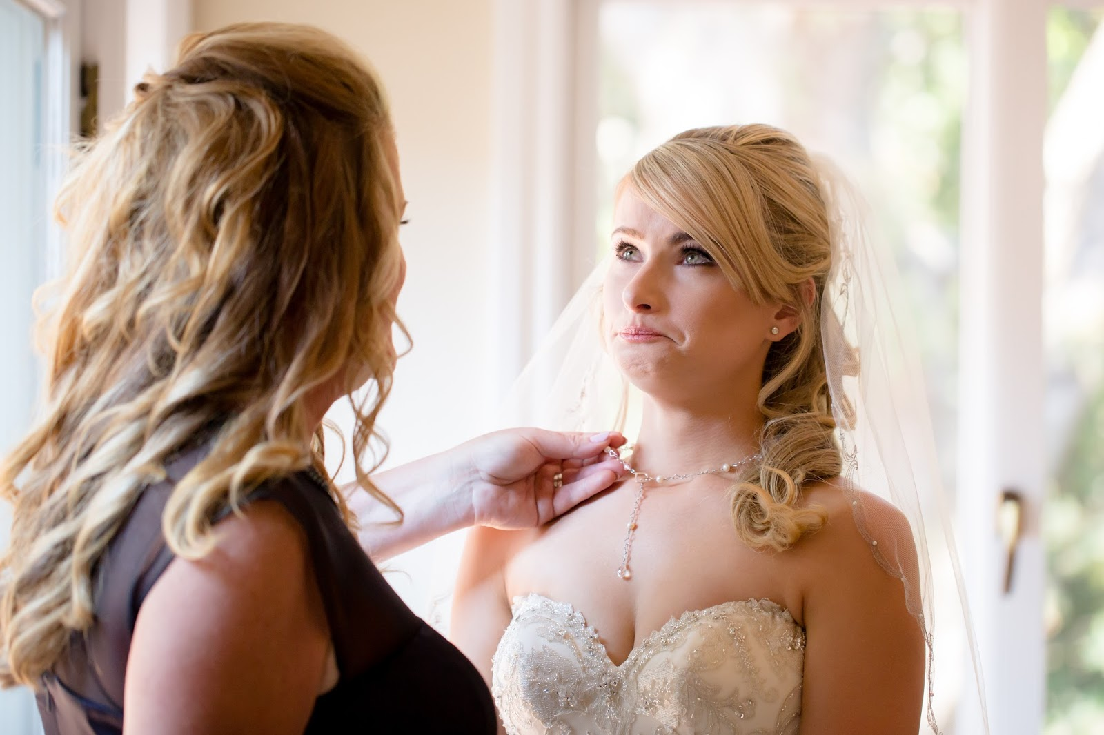 Bride holding back tears with mom