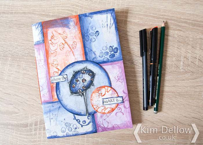 The altered patterned paper cover by Kim Dellow