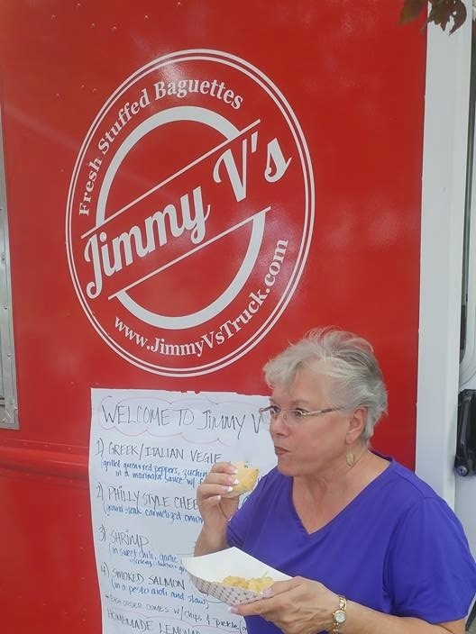 Angel enjoys her Fresh Stuffed Baguette outside Jimmy Vs Food Truck Event