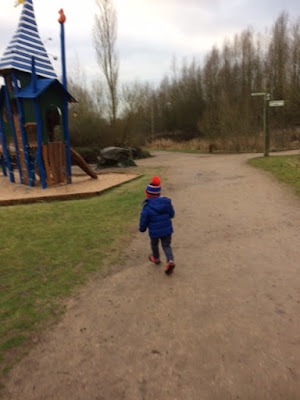 Little boy running towards a park